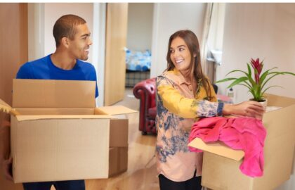Image of two people standing in a flat holding cardboard boxes